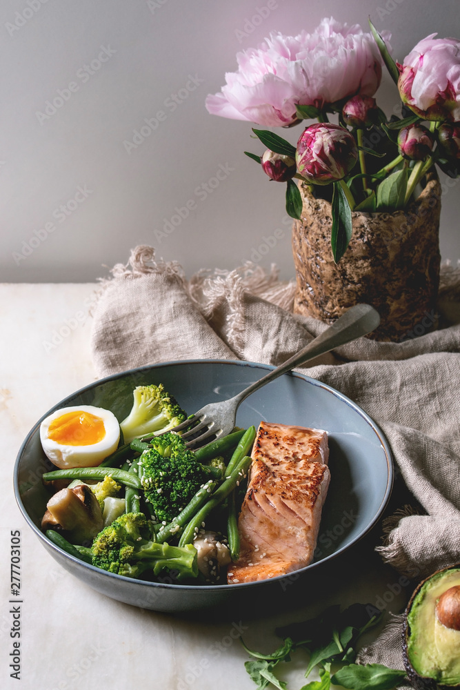 Fototapety, obrazy: Ketogenic low carb diet dinner grilled salmon, avocado, broccoli, green bean and soft boiled egg in ceramic bowl served with olives and nuts, bouquet of peonies on grey table.