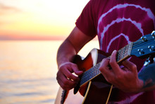 Young Man Wearing Purple Tie Dye T-shirt Playing Dreadnought Parlor Acoustic Guitar On Beach At Beautiful Sunset Time. Fit Guitarist W/ Sunburst Instrument By The Sea. Background, Copy Space, Close Up