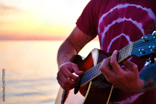 Young man wearing purple tie dye t-shirt playing dreadnought parlor acoustic guitar on beach at beautiful sunset time. Fit guitarist w/ sunburst instrument by the sea. Background, copy space, close up - 277703913