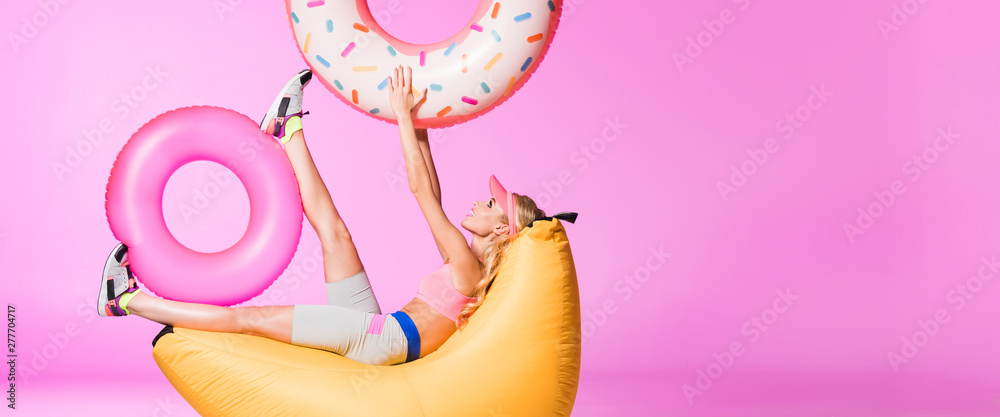 Fototapety, obrazy: panoramic shot of girl on bean bag chair with inflatable swim rings on pink, doll concept