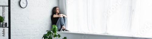 panoramic shot of depressed young woman sitting on window sill with crossed arms and looking away