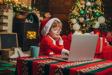 Buy Christmas Gifts Online. Christmas Shopping Concept. Gifts Service. Little Genius. Santa Little Helper. Boy Child With Laptop Near Christmas Tree. Little Boy Santa Hat And Costume Having Fun