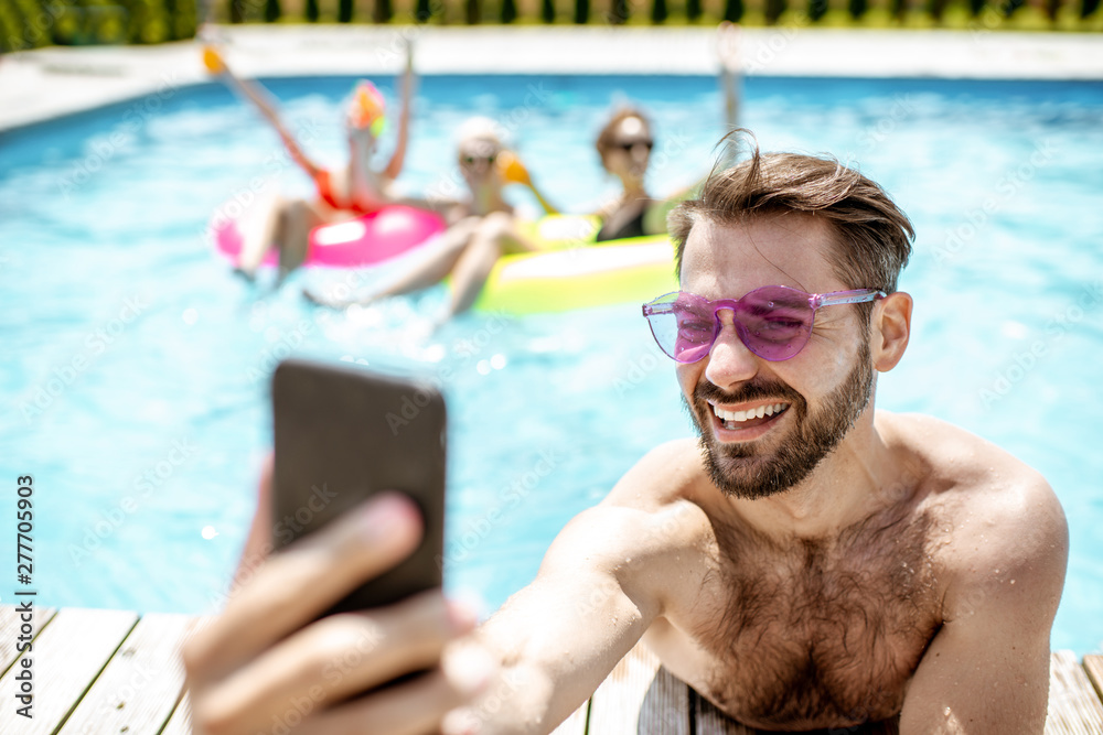 Fototapety, obrazy: Handsome man takng selfie photo with phone, while resting in the swimming pool with friends outdoors during the summertime