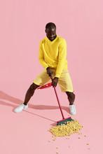 Black Man Sweeping Pop Corn On Floor On Pink Background