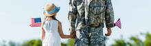 Panoramic Shot Of Patriotic Child And Man In Military Uniform Holding Hands And American Flags