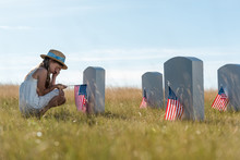 Selective Focus Of Child Covering Face While Sitting Near Headstones With American Flags