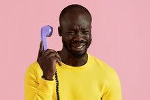 Black Man Crying, Talking On Phone On Pink Background Portrait