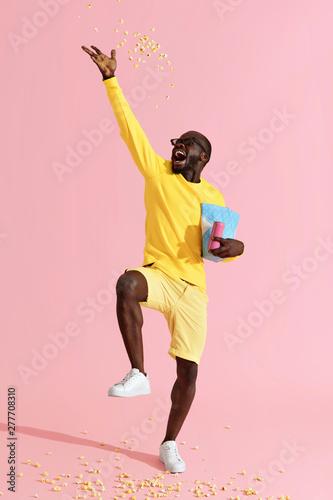 Happy man in cinema glasses having fun throwing pop corn in air