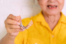 Asian Elderly Woman Over 70 Years Old Be Smile With A Few Broken Teeth And Holding Dentures In Hand. Dentures For Prosthetic Devices Constructed To Replace Missing Teeth And Helping To Chew Food.