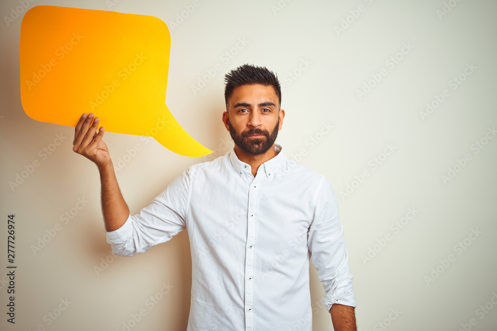 Fototapeta Young arab indian hispanic man holding speech bubble over isolated white background with a confident expression on smart face thinking serious