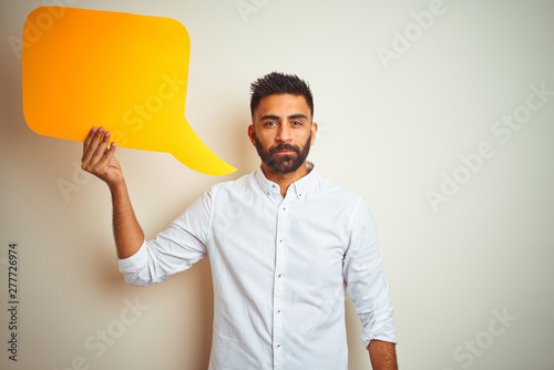 Obraz Young arab indian hispanic man holding speech bubble over isolated white background with a confident expression on smart face thinking serious - fototapety do salonu