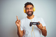 Leinwandbild Motiv Arab indian gamer man playing video game using headphones over isolated white background very happy pointing with hand and finger to the side