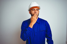 Handsome Indian Worker Man Wearing Uniform And Helmet Over Isolated White Background Bored Yawning Tired Covering Mouth With Hand. Restless And Sleepiness.