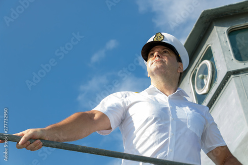 Fototapeta Captain standing on the gallery of navigation bridge of ship and  looking ahead