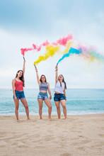 Happy Teenage Girls Holding Colored Smoke Bombs And Having Fun On The Beach