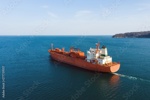 Aerial view of sea vessel for transportation of a cargo vessel at high speed is drifting near the seaport of the city at sunset Canvas Print