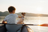 Fototapeta Zwierzęta - Happy boy with his dog Jack Russell Terrier paddling an inflatable kayak on the water mountain lake against the backdrop of beautiful orange sunset. Family sports vacation. Lens flare. Pet