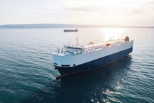 Aerial View Of High-speed Sea Vessel For Transportation Of Cargo Vessel At High Speed Is Drifting Near The Seaport Of The City At Sunset. Ship On The Background Of Blue Sea Water. Import, Export. Top