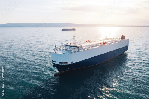 Foto Aerial view of high-speed sea vessel for transportation of cargo vessel at high speed is drifting near the seaport of the city at sunset