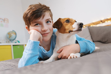 Portrait of a happy boy and his dog breed Jack Russell Terrier, who sit and cuddle on a gray bedspread over the bed and affectionately looking at his owner against the bokeh background of bright light