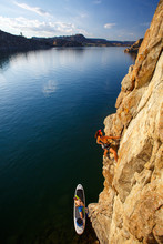You've Heard Of SUP Yoga But What About SUP Climbing? A Woman Rock Climbs  While A Man Belays Below From A SUP Board At Banks Lake In Central Washington.