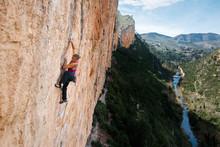 Woman Climbing On Rock