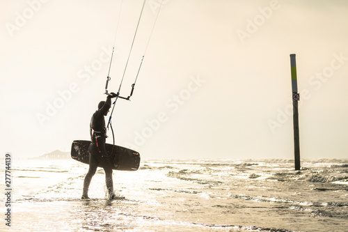 Man with surfboard holding Kiteboarding gear on beach during sunset