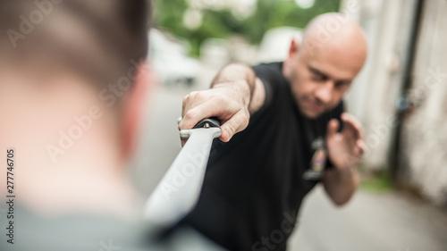 plakat Eskrima and kapap instructor demonstrates machete weapon fighting technique