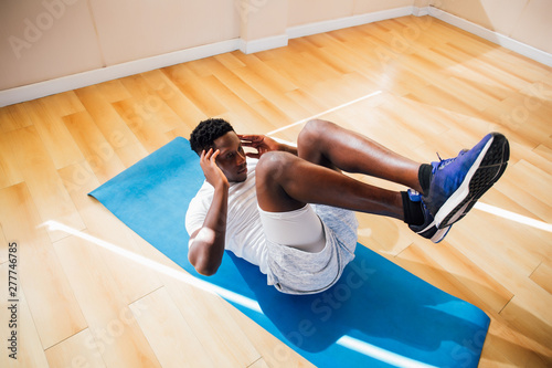 Top view of young African American man doing sit-up exercise on yoga mat at gym Fototapeta