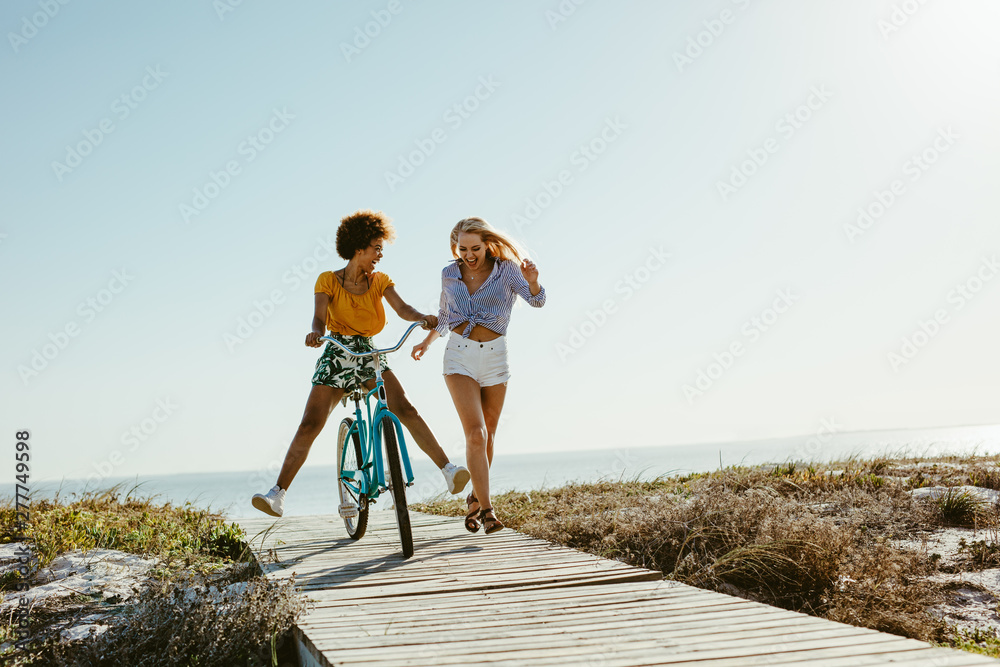 Fototapety, obrazy: Two women having fun with a bicycle at beach