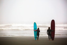Rear View Of Surfers Holding Surfboards While Standing On Beach