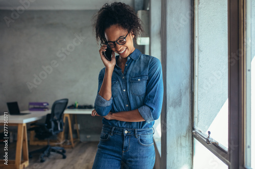 Positive woman in office talking on phone