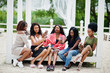 canvas print picture - Group of five african american girls relaxing at beautiful poolside cabana beside luxury resort and looking at mobile phones.