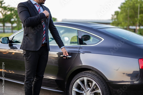Handsome young chauffeur holding the door of a car Poster Mural XXL
