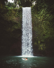 Man Swimming Under Waterfall
