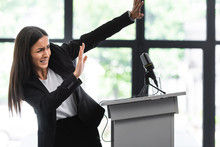 Scared Lecturer Suffering From Fear Of Public Speaking Gesturing With Hands While Standing On Podium Tribune In Conference Hall