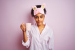 Afro woman wearing pajama and mask drinking a cup of coffee over isolated pink background with a confident expression on smart face thinking serious