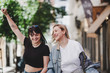 Cheerful lesbians holding hands and waving LGBT flag while walking on blurred background of city street