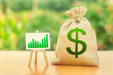 Money Bag With Dollar Symbol And A Stand With A Green Growth Trend Chart. Increase Profits And Wealth. Growth Of Wages. Favorable Conditions For Business. Investment Attraction. Loans And Subsidies