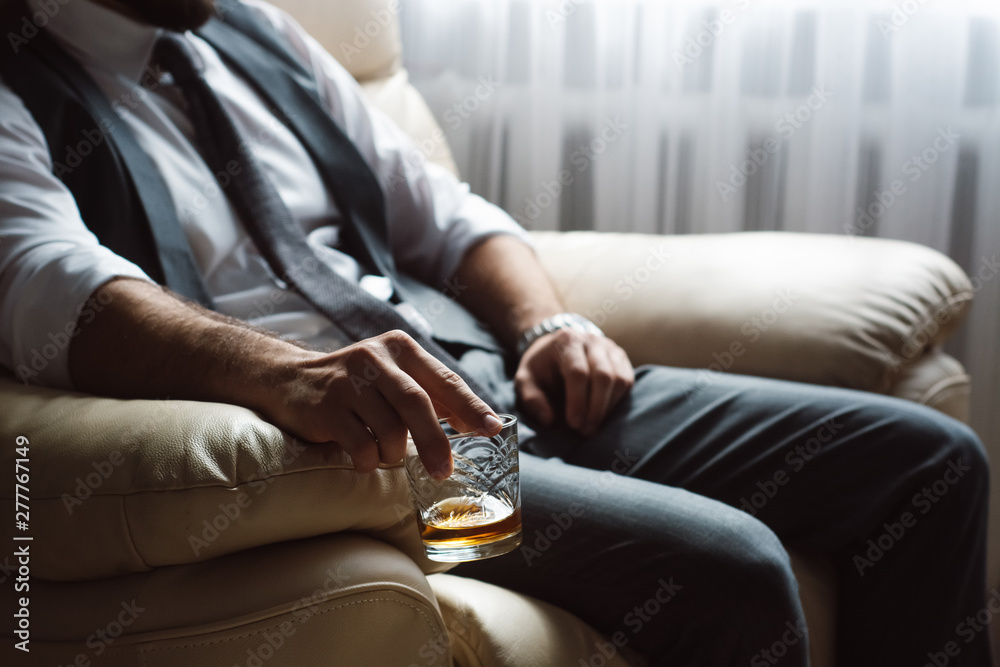 Fototapeta Image of young man holds glass of brandy. Tasting and degustation concept. Businessman in elegant suit with glass of whiskey. Sommelier tastes expensive drink.