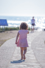 Back View Of Curly Child In Striped Summer Dress Going Along Walkway On Beach On Blurred Nature Background