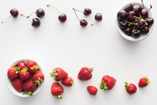 Top View Of Sweet Strawberries And Whole Cherries On Bowls