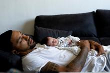 Father With Newborn Baby Sleep...