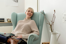 Happy Woman Sitting In Armchair At Home With Tablet