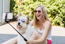 Happy Woman Taking A Selfie With Her Dog Wearing Sunglasses