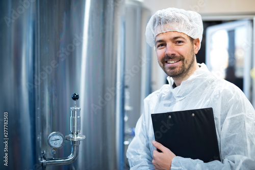 Photo  Technologist in white protective uniform and hairnet standing by chrome reservoirs with pressure gauge in food processing plant