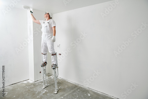Fényképezés  Painter worker on stilts with roller painting ceiling into white