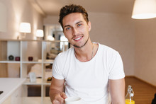 Indoor Portrait Of Pleased Brunette Man With Beard Posing With Cup Of Tea In His Apartment. Photo Of Tanned Guy With Pretty Smile Enjoying Coffee In Morning.