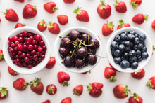 Top View Of Sweet Blueberries, Cherries And Cranberries On Bowls And Strawberries On Background