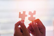 jigsaw puzzle with woman hand connecting jigsaw piece with sunlight / Business solutions partnership success and strategy